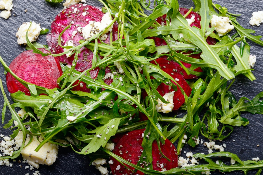 Beetroot arugula and feta cheese salad on slate stone plate clos